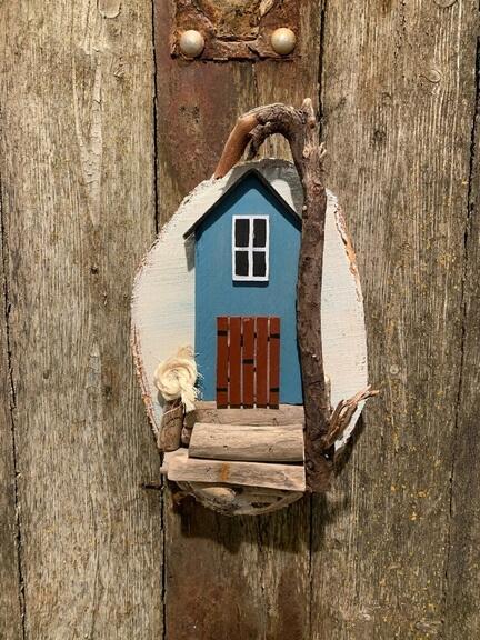 chamerende blåt hus af drivtømmer på træ skive