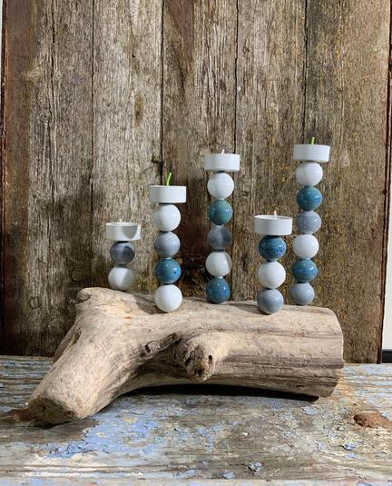 lysestage med porcelæns kugler på drivtømmer